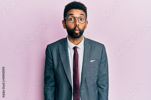Papel de parede Handsome hispanic business man with beard wearing business suit and tie making fish face with lips, crazy and comical gesture