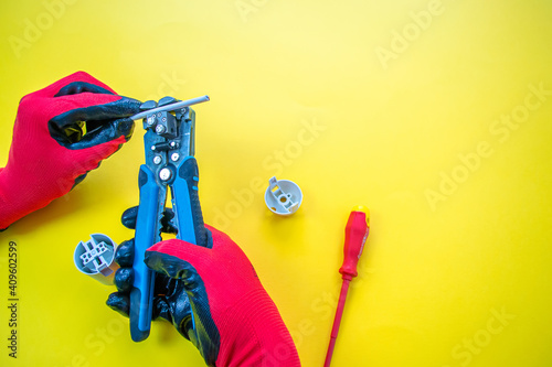Fotografie, Obraz Electrician peeling off insulation from wires - closeup on hands and pliers