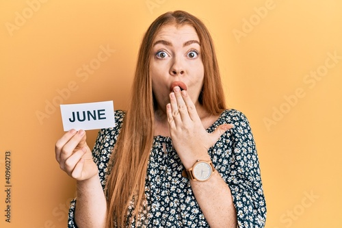 Obraz Young beautiful redhead woman holding june word on paper covering mouth with hand, shocked and afraid for mistake. surprised expression - fototapety do salonu