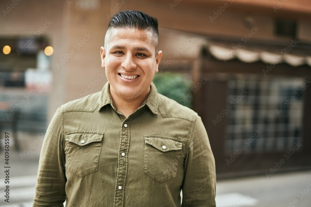 Fototapeta Young latin man smiling happy standing at the city.