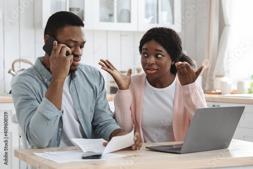Obraz Worry Black Couple Sitting In Kitchen With Financial Papers, Calling To Bank - fototapety do salonu