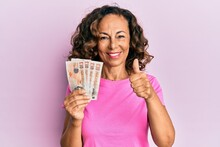 Middle Age Hispanic Woman Holding United Kingdom Pounds Smiling Happy And Positive, Thumb Up Doing Excellent And Approval Sign