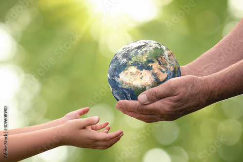Obraz Close up of senior hands giving small planet earth to a child over defocused green background with copy space - fototapety do salonu