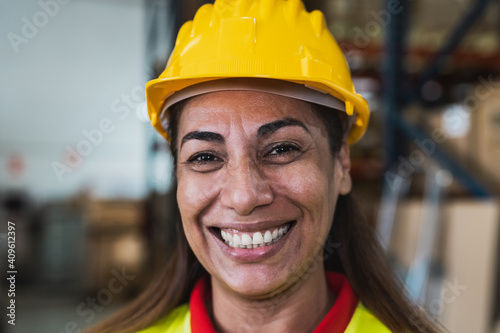 Tableau sur Toile Portrait of happy Latin woman working in delivery warehouse - Logistic and indus