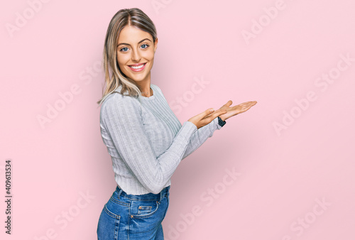 Fotografia Beautiful blonde woman wearing casual clothes pointing aside with hands open pal