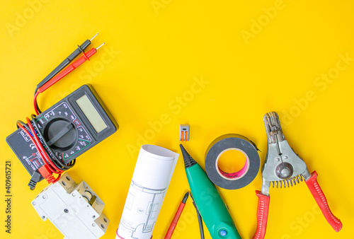 Fototapeta Electrician peeling off insulation from wires - closeup on hands and pliers