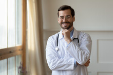 Portrait Of Smiling Young Caucasian Male Doctor In White Medical Uniform Look At Camera Show Confidence Success. Happy Millennial Man GP Or Pediatrician Feel Optimistic In Private Hospital Or Clinic.