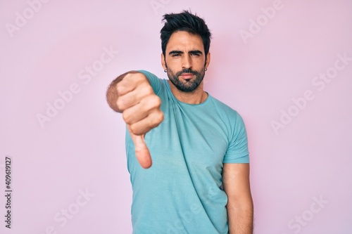 Tela Handsome hispanic man with beard wearing casual clothes looking unhappy and angry showing rejection and negative with thumbs down gesture