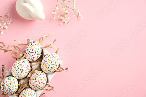 Happy Easter concept. Cute Easter eggs, bunny and spring flowers on pink table. Flat lay, top view, copy space.