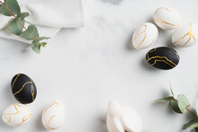 Luxury Easter Flat Lay Composition With Black And Golden Eggs, Eucalyptus Leaves, Bunny Rabbit, Towel On Marble Table. Happy Easter Concept. Top View.