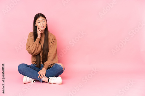 Young asian woman sitting on the floor isolated on pink background thinking an idea while looking up © luismolinero
