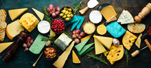 Big Set Of Cheese, Nuts, Grapes And Snacks On A Black Stone Background. Free Copy Space. Top View.