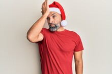 Middle Age Handsome Man Wearing Christmas Hat And Summer T-shirt Surprised With Hand On Head For Mistake, Remember Error. Forgot, Bad Memory Concept.