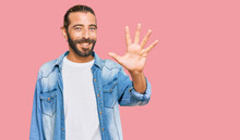Attractive Man With Long Hair And Beard Wearing Casual Denim Jacket Showing And Pointing Up With Fingers Number Five While Smiling Confident And Happy.