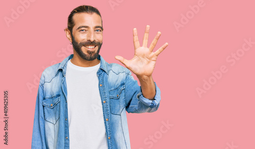 Attractive man with long hair and beard wearing casual denim jacket showing and pointing up with fingers number five while smiling confident and happy Fototapeta