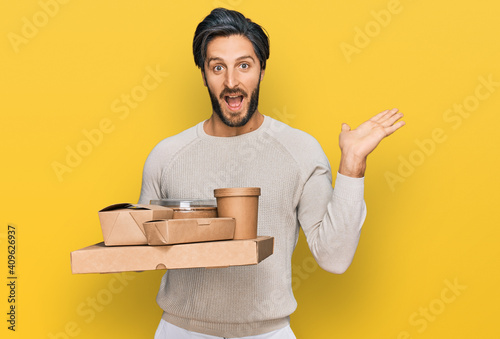 Young hispanic man holding take away food celebrating victory with happy smile and winner expression with raised hands