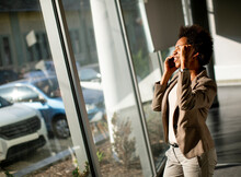 African American Business Woman Using Mobile Phone By The Window In The Office