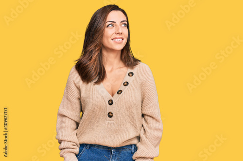 Canvas Young brunette woman wearing casual winter sweater looking away to side with smile on face, natural expression
