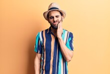 Young Handsome Man With Beard Wearing Summer Hat And Shirt Touching Mouth With Hand With Painful Expression Because Of Toothache Or Dental Illness On Teeth. Dentist