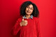 Leinwandbild Motiv Beautiful african american woman with afro hair wearing sweater and glasses doing happy thumbs up gesture with hand. approving expression looking at the camera showing success.
