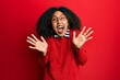 Leinwandbild Motiv Beautiful african american woman with afro hair wearing sweater and glasses celebrating crazy and amazed for success with arms raised and open eyes screaming excited. winner concept