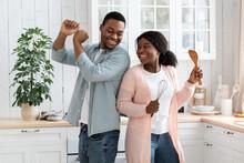 Happy African Couple Having Fun In Kitchen, Dancing With Utencils In Hands