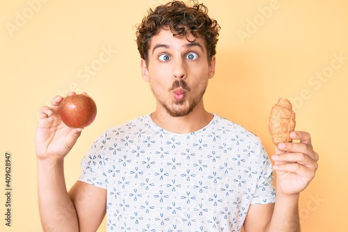 Carta da parati Young caucasian man with curly hair holding apple and croissant making fish face with mouth and squinting eyes, crazy and comical