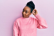 Young African American Woman Wearing Casual Winter Sweater Confuse And Wondering About Question. Uncertain With Doubt, Thinking With Hand On Head. Pensive Concept.