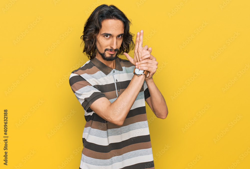 Fototapeta Young hispanic man wearing casual clothes holding symbolic gun with hand gesture, playing killing shooting weapons, angry face