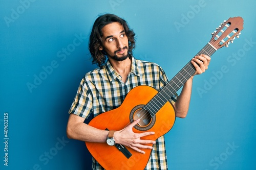Fotografie, Obraz Young hispanic man playing classical guitar smiling looking to the side and staring away thinking
