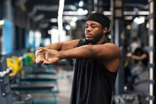 Athletic Black Guy Stretching Hands In Gym