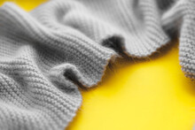 Blurred Gray Knitted Scarf Asymmetrical Frame  On Yellow .  Symbolize Warmth, Love And Tenderness.  Valentine's Day Concept. Trendy Color 2021. Copy Space