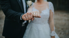 Closeup Shot Of A Bride And Bridegroom Fist Showing Their Wedding Rings