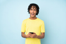 Young African American Man Isolated On Blue Background Surprised And Sending A Message
