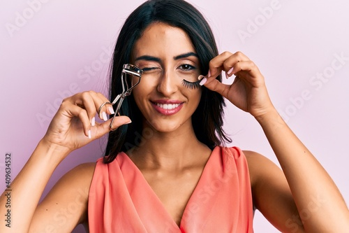 Fotografie, Obraz Beautiful hispanic woman holding eyelash curler and fake lashes winking looking at the camera with sexy expression, cheerful and happy face