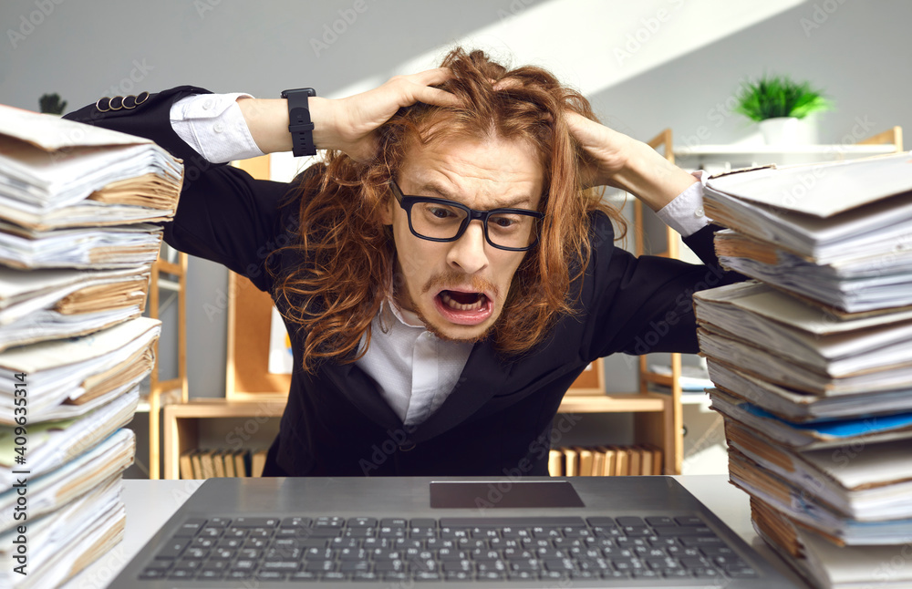 Fototapeta Crazy weird stressed young guy in glasses having busy day at work, sitting at office desk with computer, tearing hair in despair exhausted by much paperwork, huge file archive, red tape workload chaos