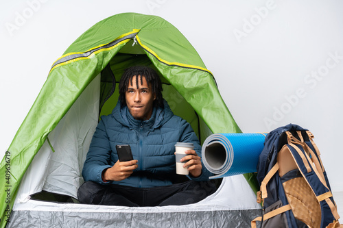 Foto Young african american man inside a camping green tent holding coffee to take aw
