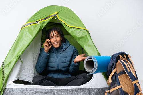 Young african american man inside a camping green tent keeping a conversation wi Fototapete