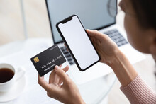 Close Up Young Woman Holding Bank Credit Card And Modern Tech Device With Mock Up White Screen In Hands, Enjoying Purchasing Goods In Internet Store Using Mobile Phone Application, Online Shopping.