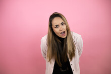 Young Beautiful Blonde Woman With Long Hair Standing Over Pink Background Afraid And Shocked With Surprise And Amazed Expression, Fear And Excited Face.