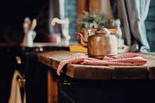 A Vintage Metal Teapot Made Of Copper Sits On A Wooden Table, With A Towel Laid Out. Stylish Old Kitchen Morning In The Village And Daylight From The Window.