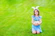 Leinwandbild Motiv Happy girl wearing bunny ears on Easter day stands on green summer grass  with basket of colorful Easter eggs. Empty space for text