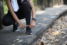 Runner Getting Ready For Jogging Tying Running Shoes Laces - Woman Preparing Before Run Putting On Trainers In  Park ,Photo Of Attractive Woman In Fashionable Sportswear. Dynamic Movement. Sport