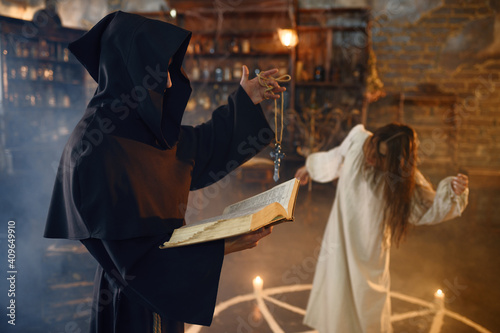 Slika na platnu Exorcist in hood casting out demons from a woman