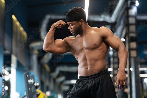 Foto Muscular black man posing and showing muscles in gym