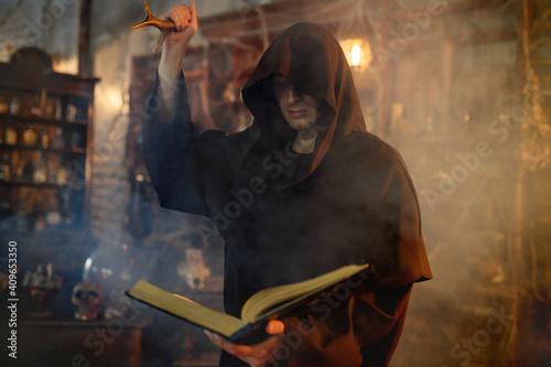 Male exorcist in black hood holds book of spells Fototapet
