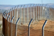 Perspective View Of A Fence With Barbed Wire In The Field
