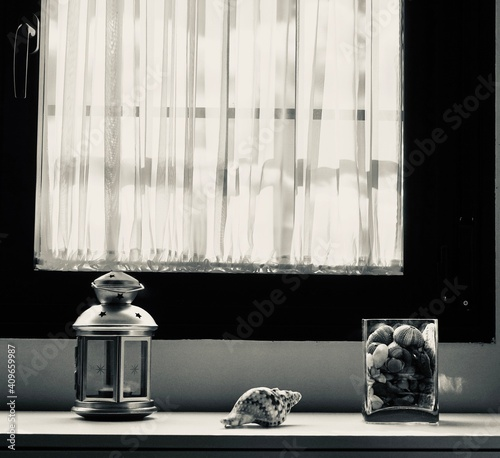 Fotografie, Obraz Black and white interior decoration: Lantern with candle, conch shell and glass