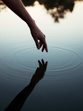 Person's Hand Touching Body Of Water With Reflection