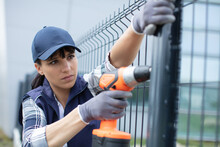 Pretty Worker Installing Welded Metal Mesh Fence